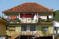 typowe gospodarstwo na Bałkanach: kwadratowy domek, suszące się pranie i papryka