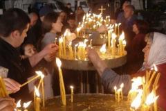 wierni zapalają modlitewne świeczki przed cerkwią